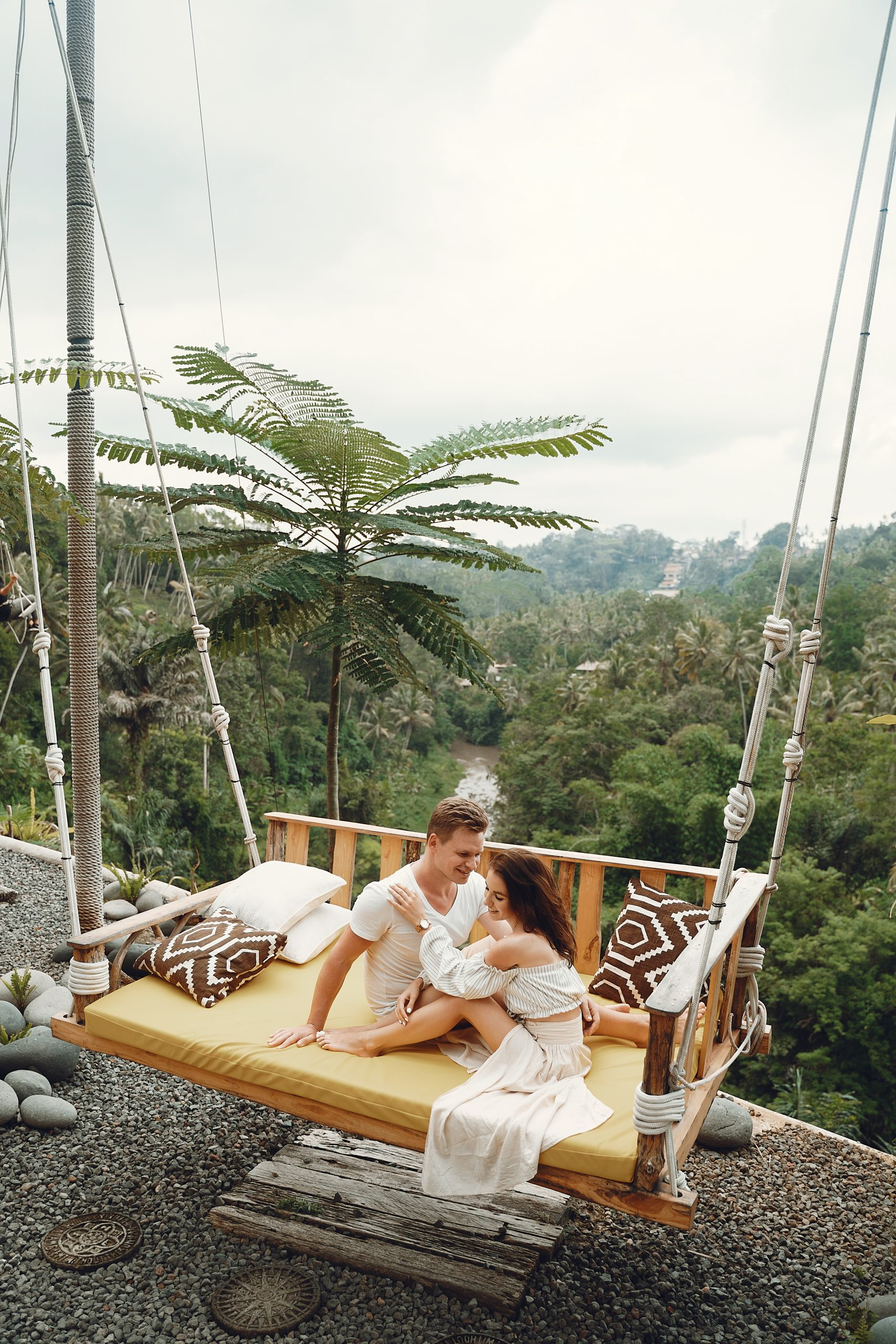 Couple assis sur une balancelle suspendu sur une terrasse