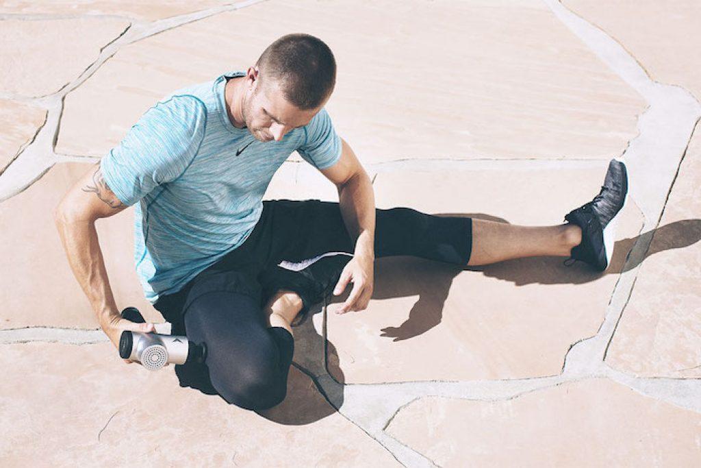 Homme se relaxant les jambes avec un pistolet de massage