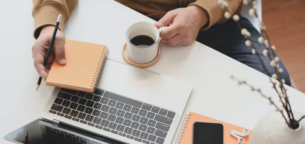 Personne travaillant sur son bureau avec bloc note café et ordinateur à la main