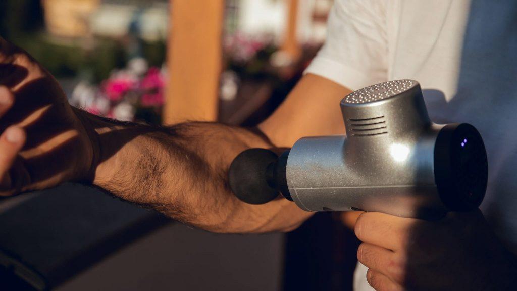 Pistolet de massage utilisé sur lavant bras par un homme