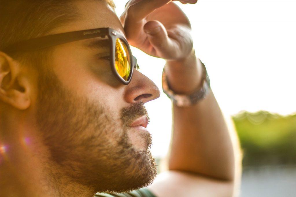 Homme barbu conduisant et portant lunette de soleil