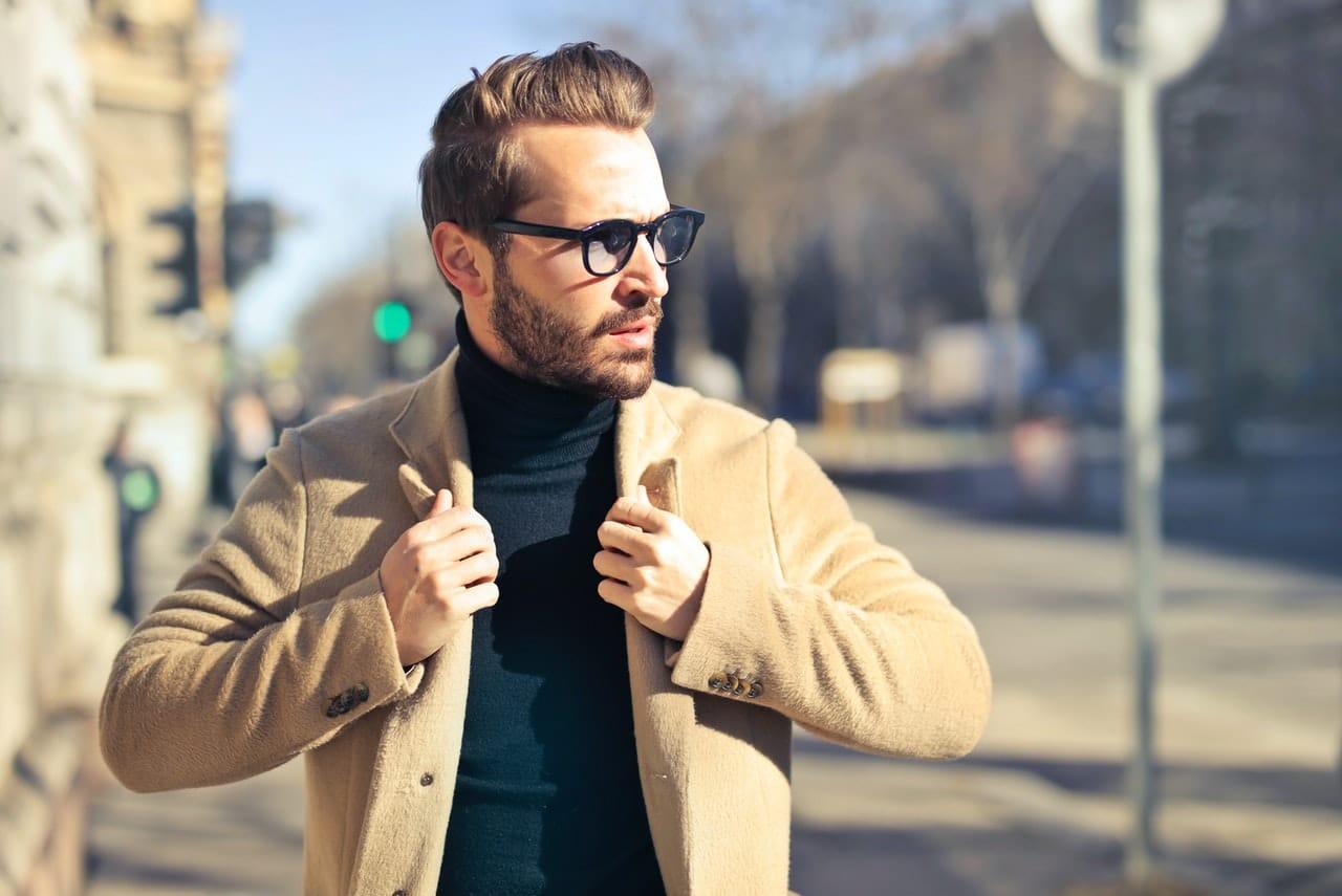 Homme marchant avec veste beige, lunette de vue et barbe de 3 jours