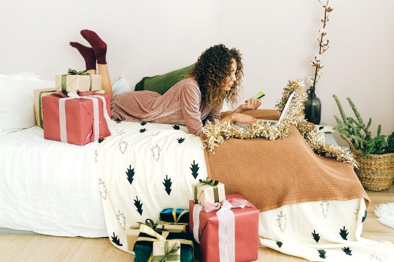Femme allongée sur son lit, faisant du shopping