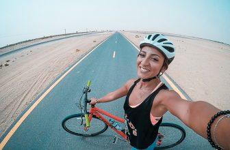 Femme heureuse, VTT, sur une route dans un desert