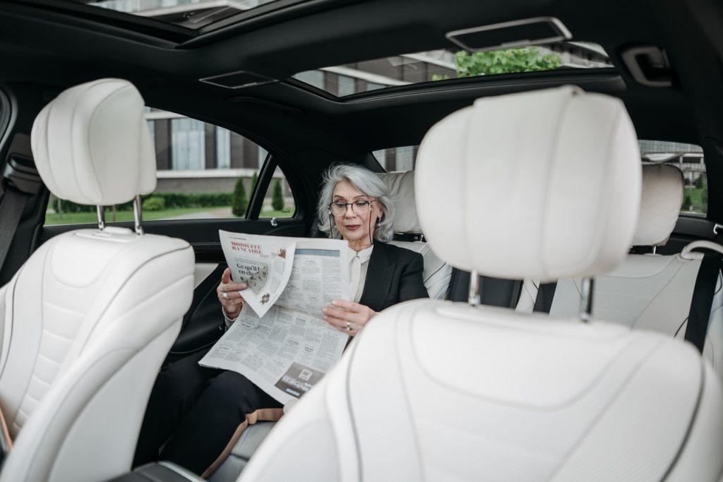 FEmme assise à l'arrière d'une voiture lisant un journal