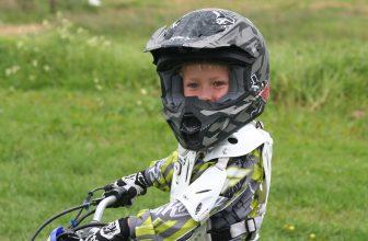 Garçon sur une moto en tenue et portant un casque