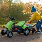 Enfant poussant tracteur à pédale avec petite remorque