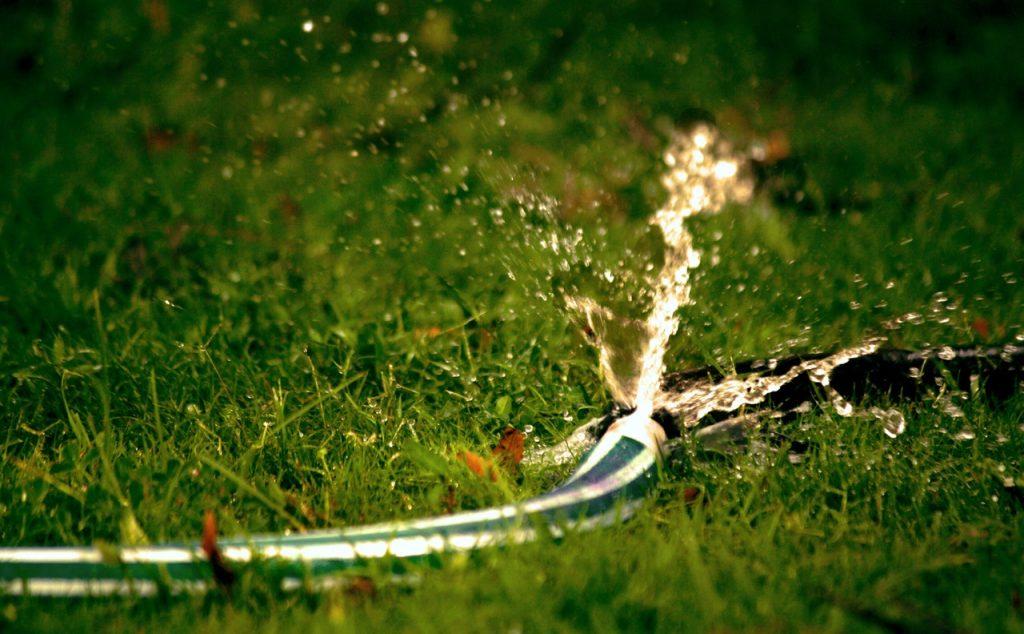 Tuyau d'arrosage ouvert avec de l'eau qui en coule